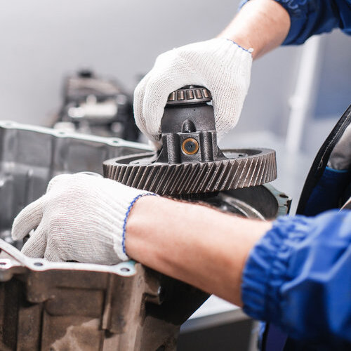 Close-up of hands working on a car transmission.